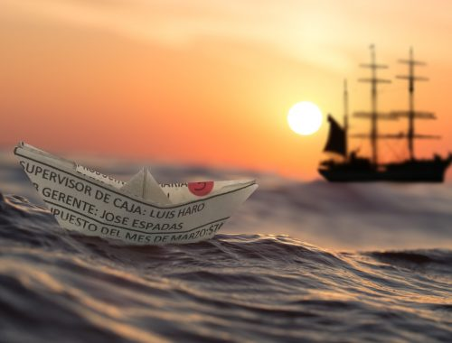 a paper boat next to a big ship in the sunset